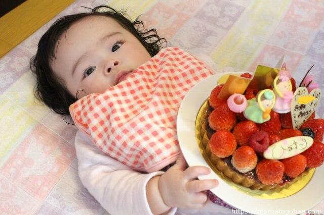 ひなまつりのケーキを持つ赤ちゃん